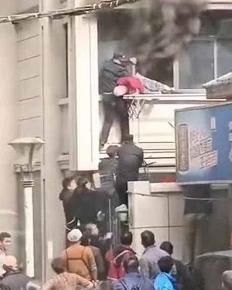"""南京一居民楼失火 城管队员搭""""人肉阶梯""""救人"""