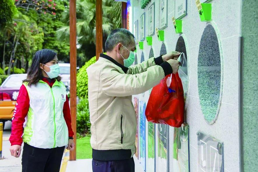 广州市白云区鹤龙街分类督导员指导居民分类投放.jpg